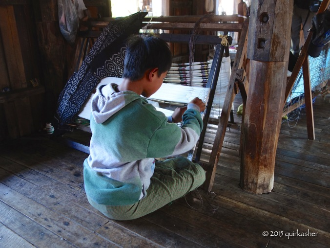 A very young boy creating patterns on threads before dying them. What was I doing at his age?