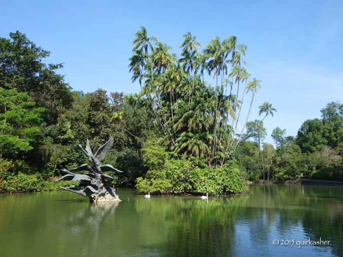 """1866 Swan Lake (Nibong palms in the middle planted in 1891) with 2006 installed """"Flight of Swans"""" sculpture"""